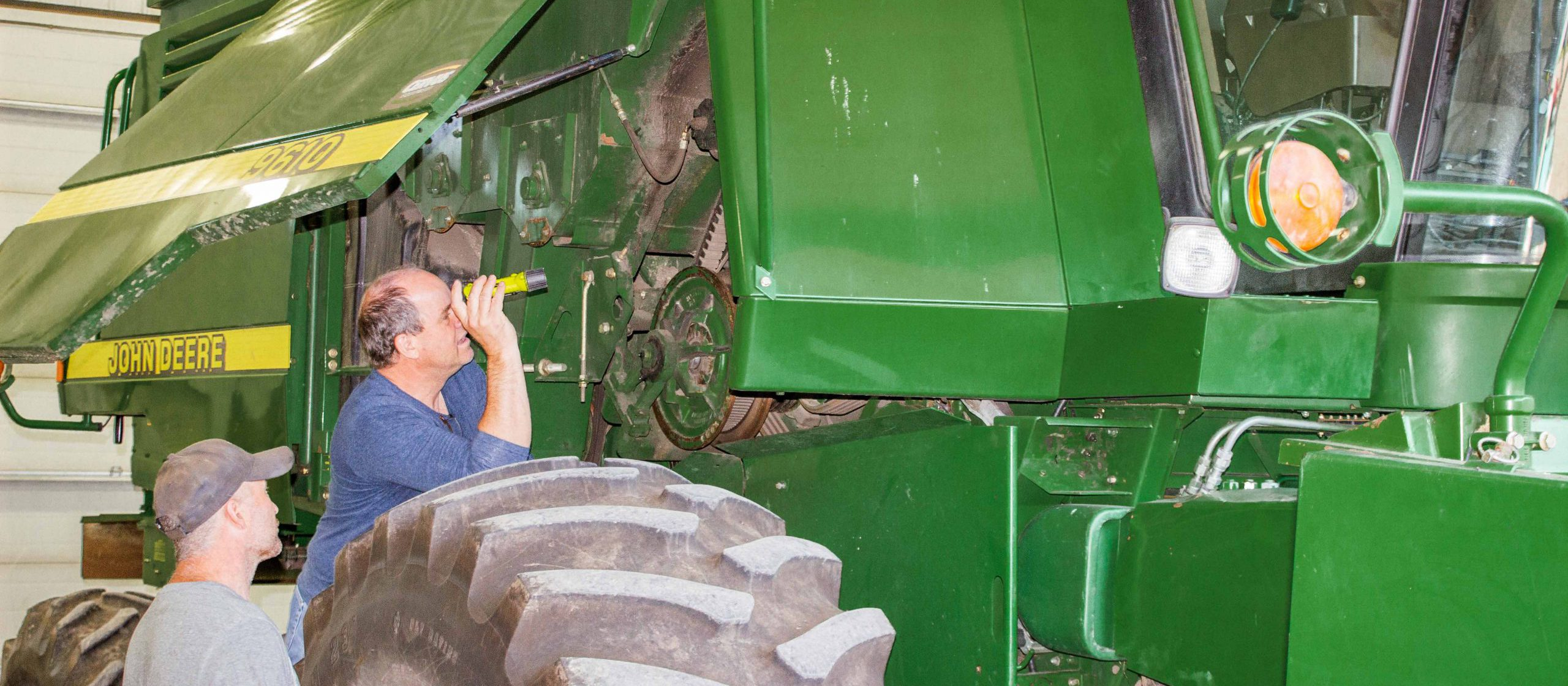 Perry Casson shining flashlight on combine
